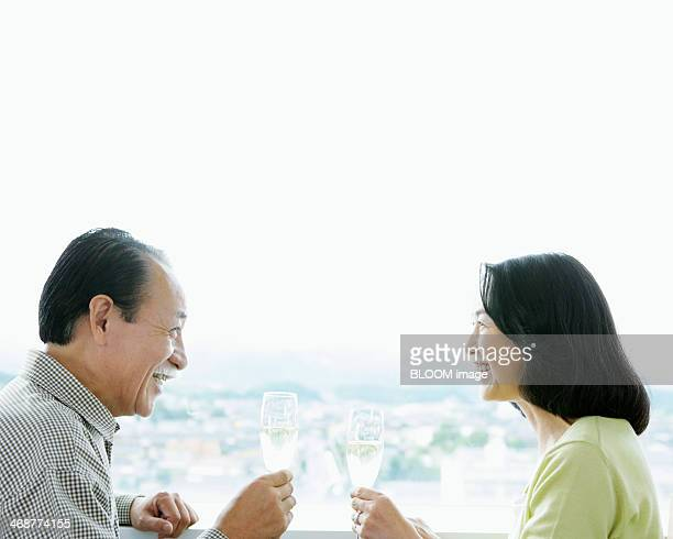 Senior Couple Toasting Glass Of Champagne