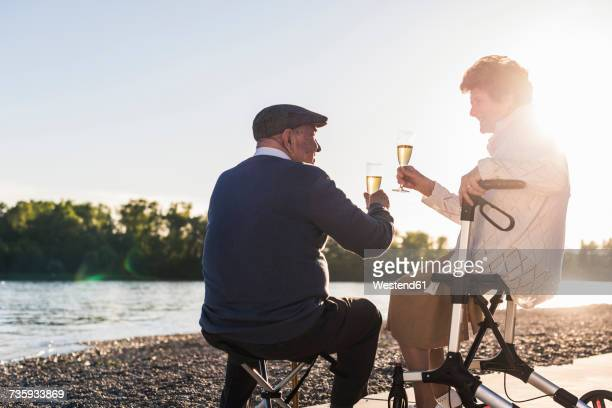 Senior couple toasting with sparkling wine at sunset