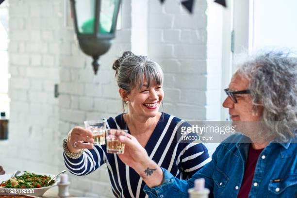 senior couple toasting with wine glasses over lunch - prosperity stock pictures, royalty-free photos & images