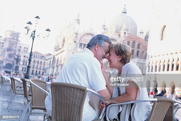 Senior couple touching foreheads at sidewalk cafe, St. Mark's Square, Venice, Veneto, Italy