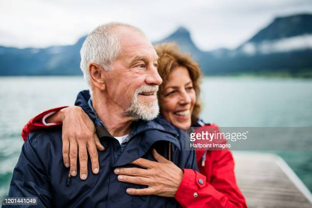senior couple tourist standing by lake in nature on holiday, hugging. - mari photos et images de collection