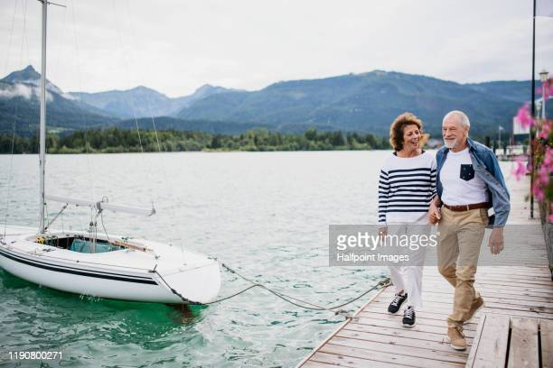 senior couple tourist walking by lake in nature on holiday, holding hands. - heteroseksueel koppel stockfoto's en -beelden