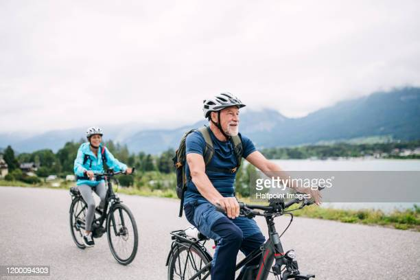senior couple tourist with bicycles cycling by lake in nature on holiday. - husband stock pictures, royalty-free photos & images