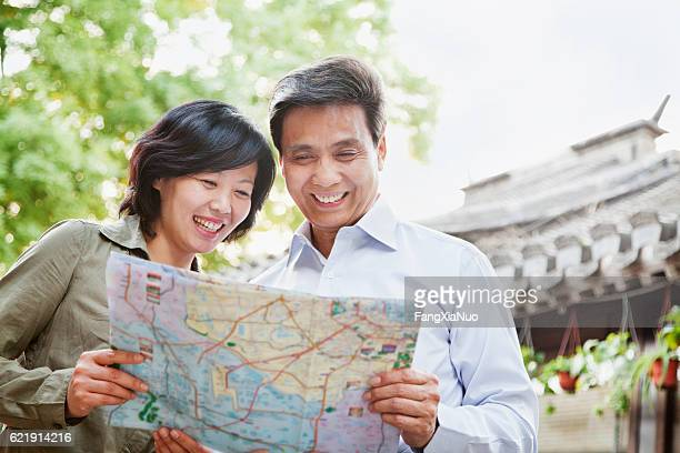 Senior couple tourists looking at map