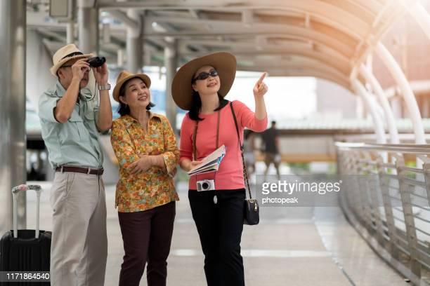 senior couple tourists looking at map ,thailand - ツアーガイド ストックフォトと画像