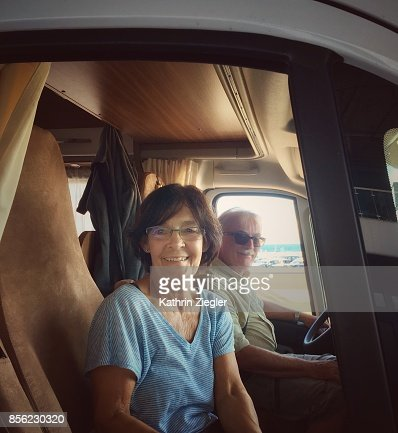 Senior couple traveling in camper, smiling