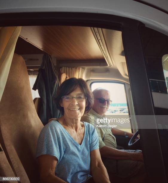 Senior couple traveling in camper, smiling