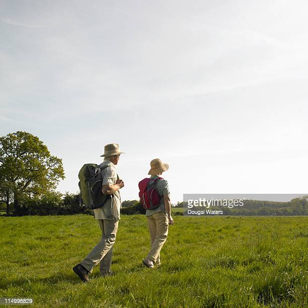 Senior couple trekking through field.