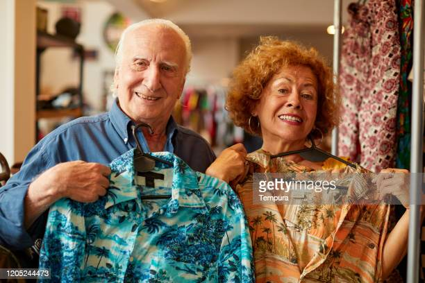 senior couple trying hawaiian shirts on and looking at camera. - bizarre fashion stock pictures, royalty-free photos & images