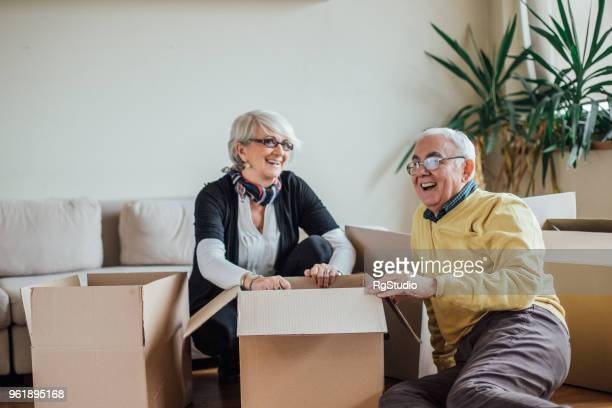 Senior couple unpacking cardboard boxes