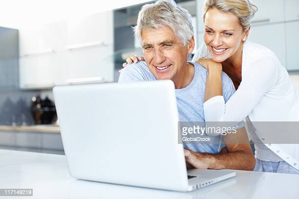 Senior couple using a laptop in the kitchen