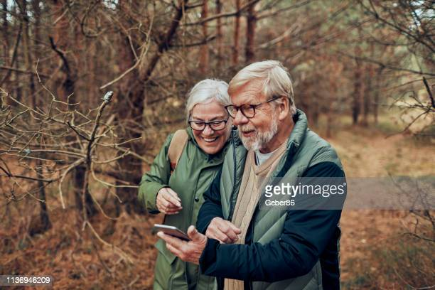 senior couple using a phone - non urban scene stock pictures, royalty-free photos & images