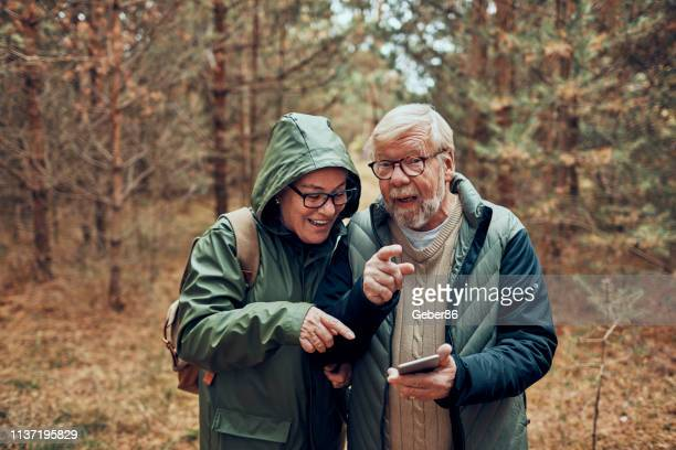 senior couple using a phone - 70 79 years stock pictures, royalty-free photos & images