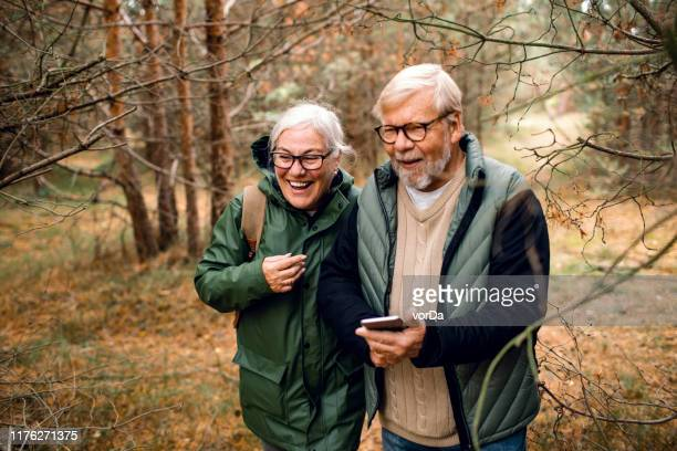 senior paar met behulp van een telefoon - wandelen stockfoto's en -beelden