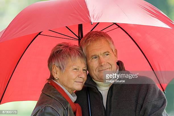 Senior couple using a red umbrella