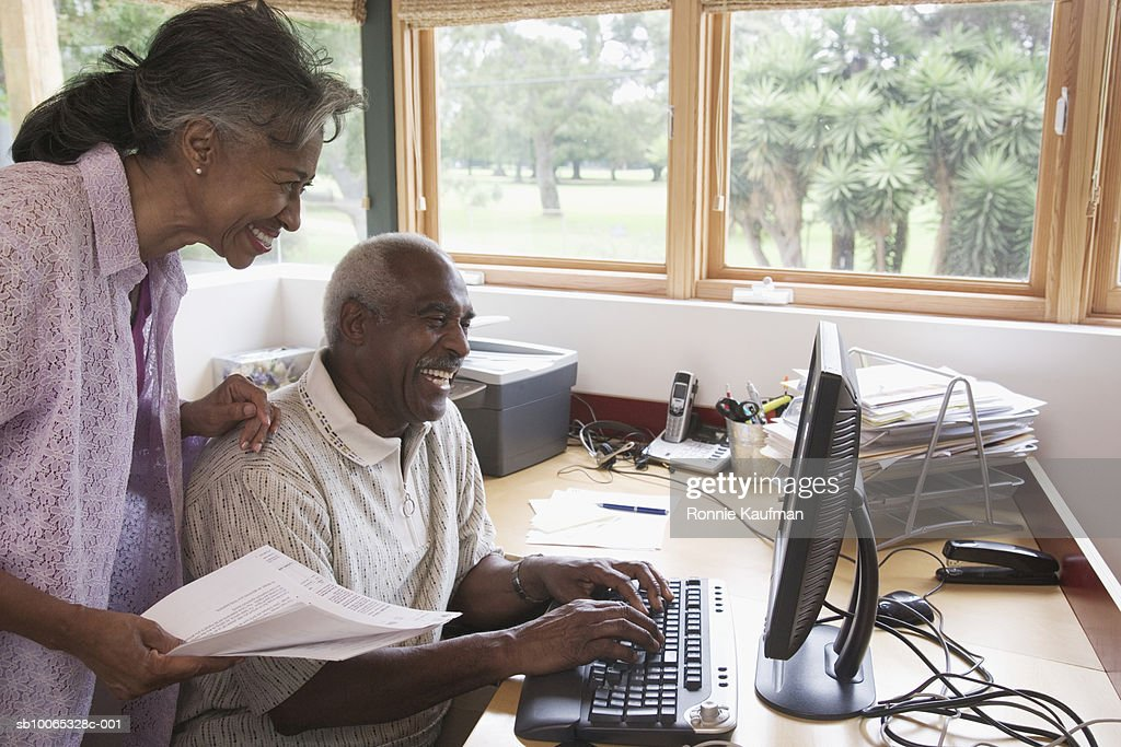 Senior couple using computer at home, smiling : Foto stock