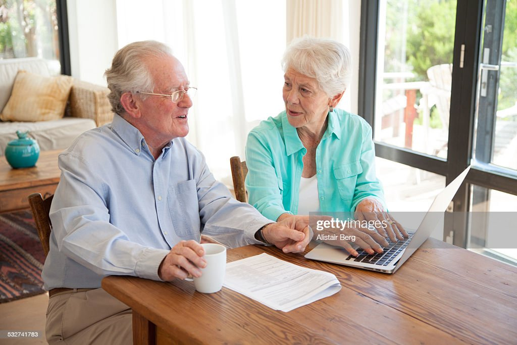 Senior couple using computer together at home : Stock Photo