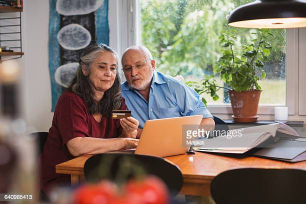 Senior couple using credit card for online payment on laptop at home