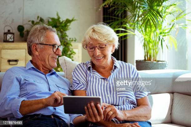 senior couple using digita tablet at home - blue stock pictures, royalty-free photos & images