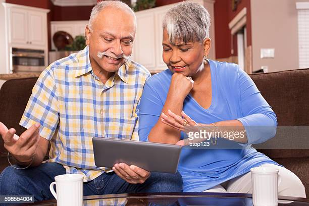 Senior couple using digital tablet computer at home.