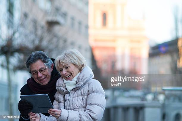 Senior couple using digital tablet in the city