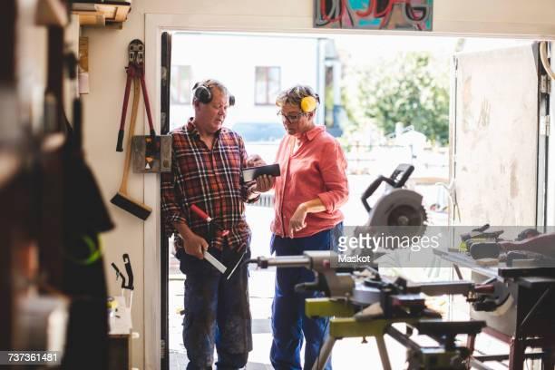 Senior couple using digital tablet while standing at workshop doorway