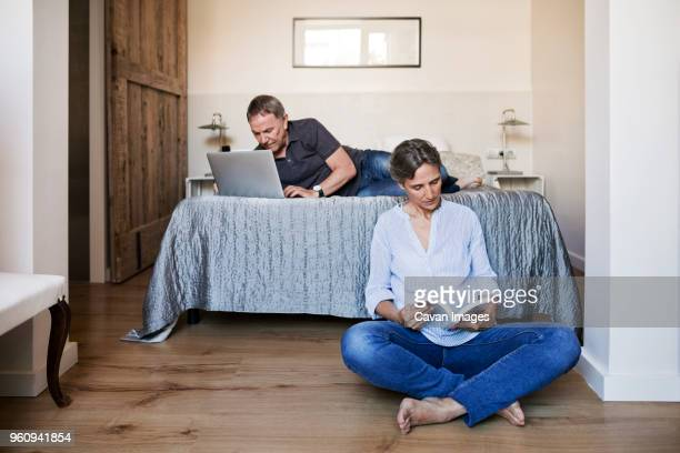 Senior couple using laptop and reading book in bedroom