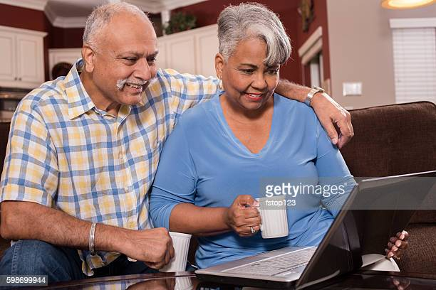 Senior couple using laptop computer at home.