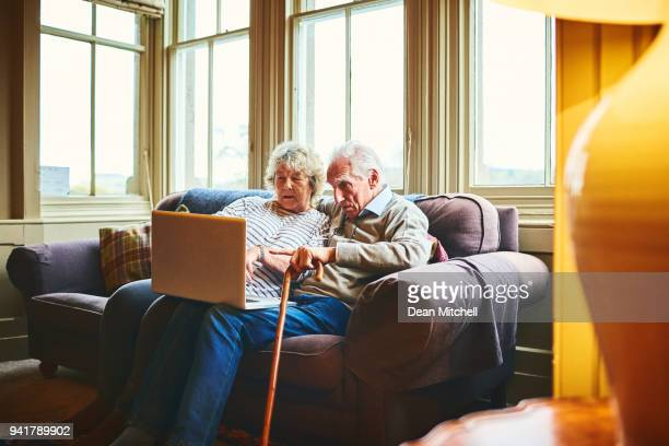 Senior couple using laptop computer together at home