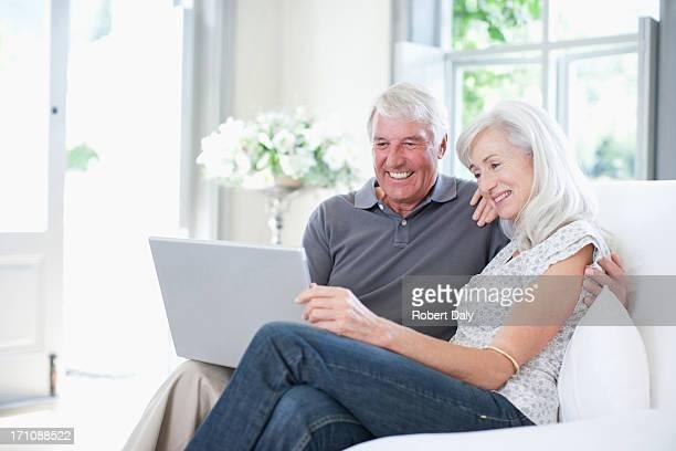 altes paar mit laptop auf sofa - 65 69 jahre stock-fotos und bilder