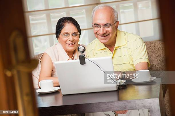 Senior couple using laptop with video conference camera