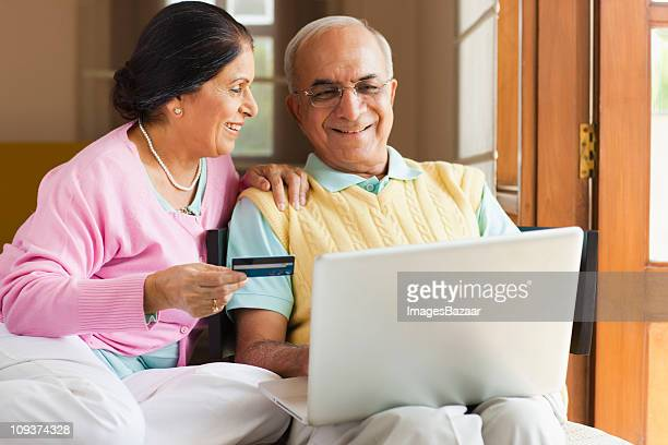 Senior couple using laptop, woman holding credit card