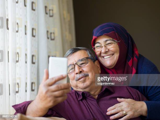 senior couple using mobile phone - middle east stock pictures, royalty-free photos & images