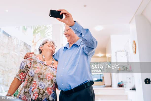 Senior couple using mobile phone to take a selfie at home