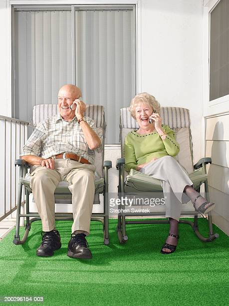 senior couple using mobile phones on patio - sun lounger stock pictures, royalty-free photos & images