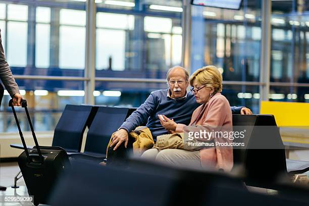 Senior Couple Using Smart Phone At Airport