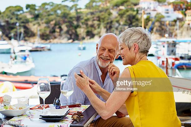 Senior couple using smart phone at restaurant