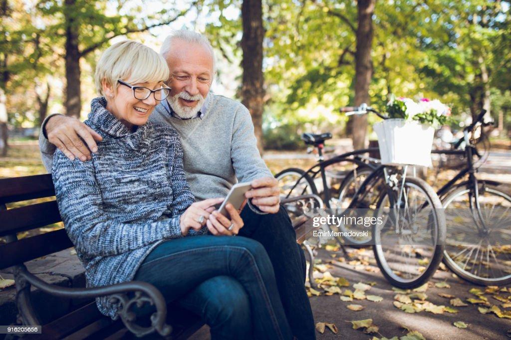 Senior couple using smart phone outdoors : Stock Photo