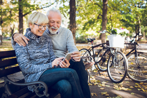 Senior couple using smart phone outdoors - gettyimageskorea
