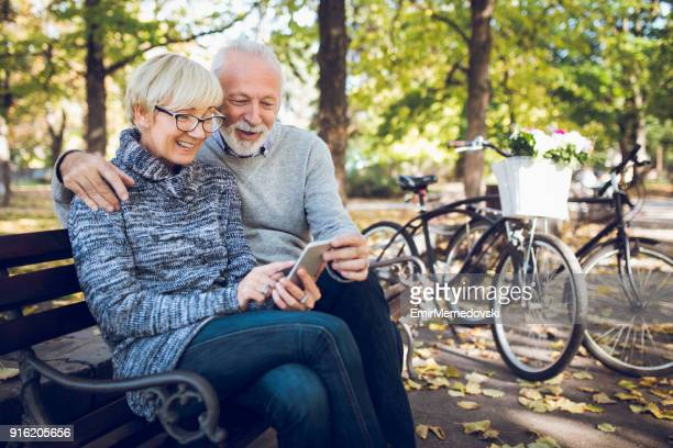 senior couple using smart phone outdoors - bench stock pictures, royalty-free photos & images