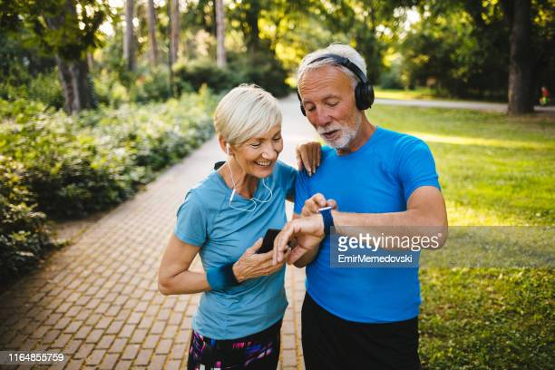 senior couple using smart watch while exercising outdoors - wearable computer stock pictures, royalty-free photos & images