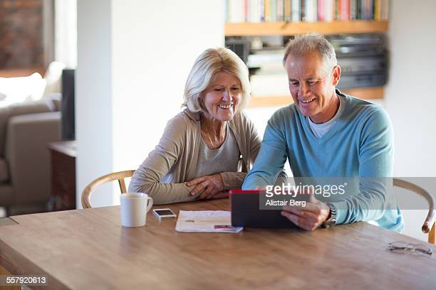 Senior couple using tablet computer at home