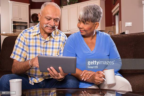Senior couple using tablet computer at home.