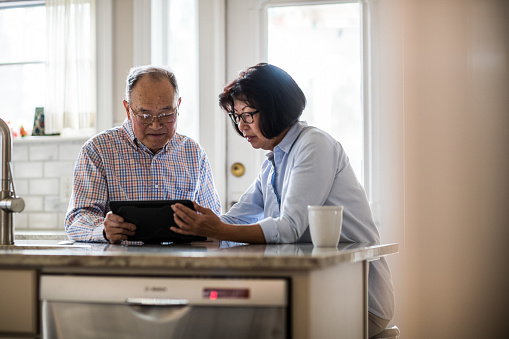 Senior couple using tablet on couch at home - gettyimageskorea