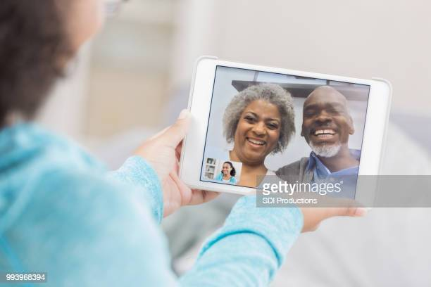 senior couple video chatting on granddaughter's device screen - facetime stock pictures, royalty-free photos & images