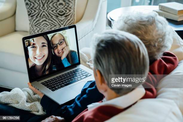 senior couple video conferencing with granddaughters through laptop computer at home - love emotion imagens e fotografias de stock
