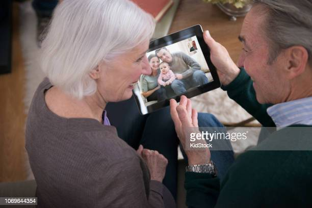 Senior couple video-chatting with granddaughter