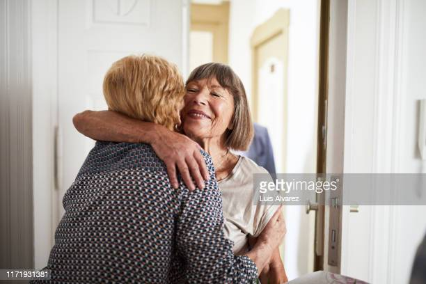senior couple visiting friends in their home - disruptaging stock pictures, royalty-free photos & images