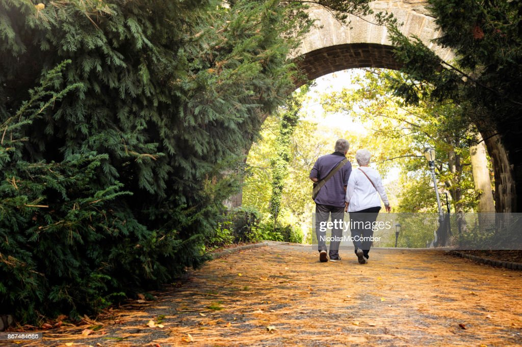 Senior couple visiting New-York City Fort Tryon park in Autumn full length rear view : Stock Photo