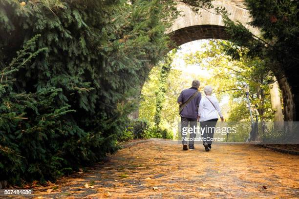 senior couple visiting new-york city fort tryon park in autumn full length rear view - happy new month stock photos and pictures